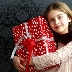 Gifts for 9 year olds - 9 year old girl holding Christmas gift