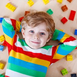 Coolest LEGO sets for kids - boy surrounded by LEGO pieces
